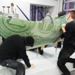 <p><strong>Beschichtung: Edelstahlblech gefaltet, Dollar-Optik, mit Klarlack versiegelt</strong><br /> Kata Legrady, Dollar-Schiffchen, 2013, 316x130x100 cm<strong><br /> </strong></p>
